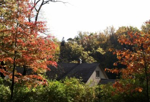 coach house barn among trees with red leaves in fall